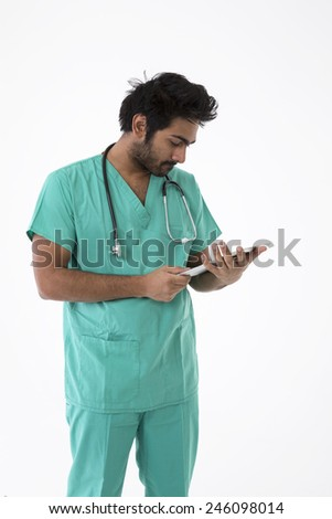 Male Indian doctor wearing a Green Scrubs & a stethoscope. Isolated on white background. - stock photo