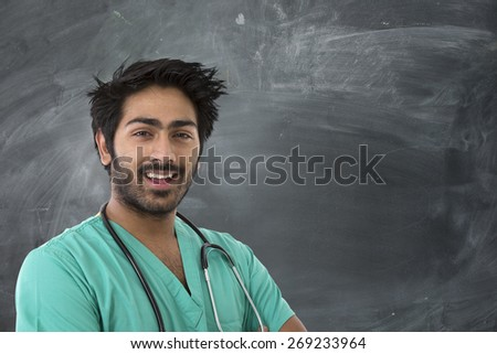 Male Indian doctor wearing a Green Scrubs & a stethoscope. Standing next to a blackboard. - stock photo