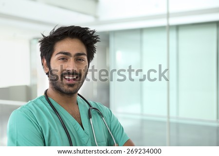 Male Indian doctor wearing a green Scrubs & stethoscope. - stock photo