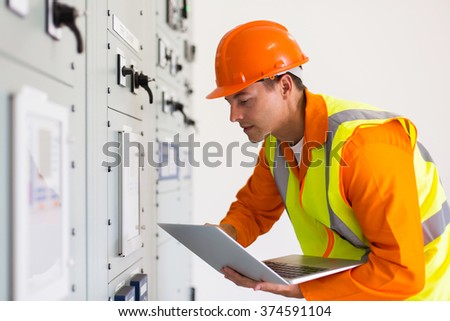 male industrial engineer using laptop in control room - stock photo