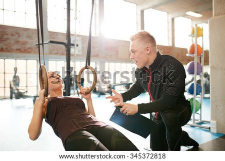 Male instructor helping a young female during a workout at gym on the rings. Personal trainer motivating young woman at health club. - stock photo