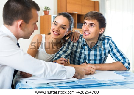Male insurance agent consulting smiling young couple in home interior
