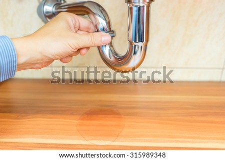 male is checking where drain pipe leaks,water on the furniture - stock photo