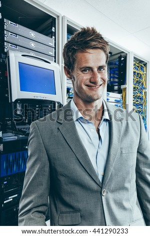 Male IT technician in front of mainframe and communication racks in data center for large organization