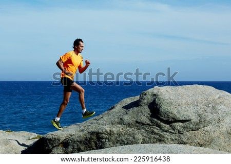 Male jogger in bright fluorescent sportswear running over rocks along the beach - stock photo