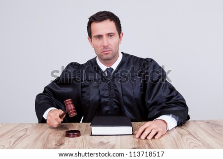 Male Judge In A Courtroom Striking The Gavel