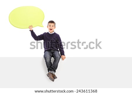 Male kid holding a speech bubble seated on panel isolated on white background - stock photo