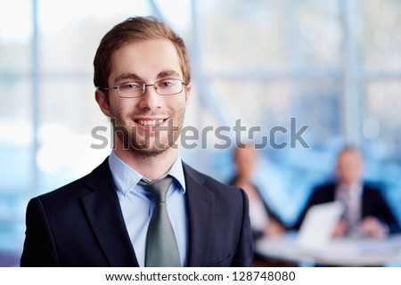 Male leader looking at camera with his partners on background - stock photo