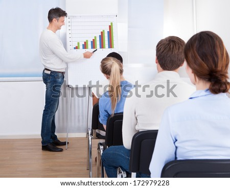Male Lecturer Explaining Diagram On Flipchart In Class - stock photo