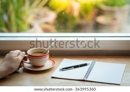 Male left hand holding coffee cup on wood bar beside window at cafe in morning time - stock photo