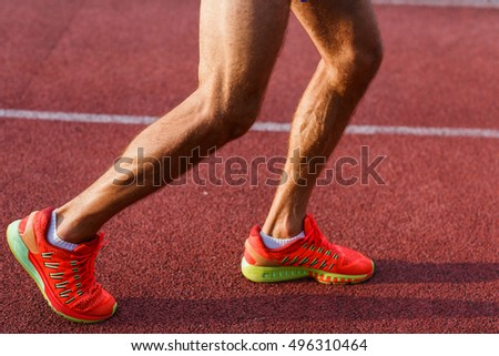 Male legs and feet on cross track outdoors