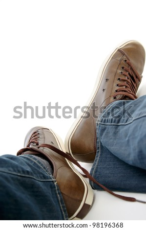 male legs in brown shoes sneakers and jeans lying down on the grownd isolated on white background - stock photo