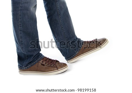 male legs in jeans and brown sneakers shoes make step isolated in white background - stock photo