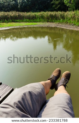 Male legs over the river - stock photo