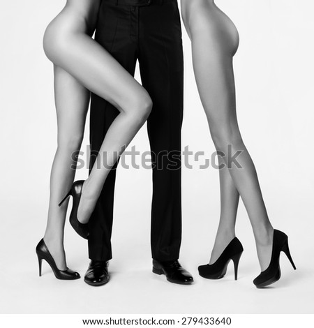 Male legs surrounded by women. Conceptual fashion art photo - stock photo