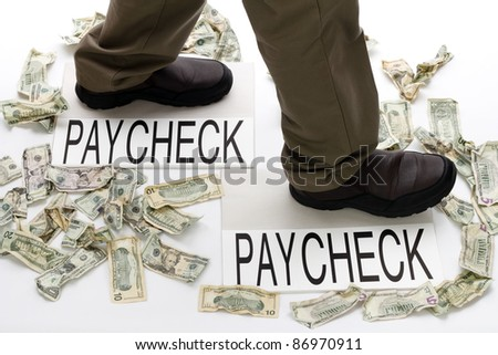Male legs walking from one paycheck to another with crumpled money scattered about on the floor.