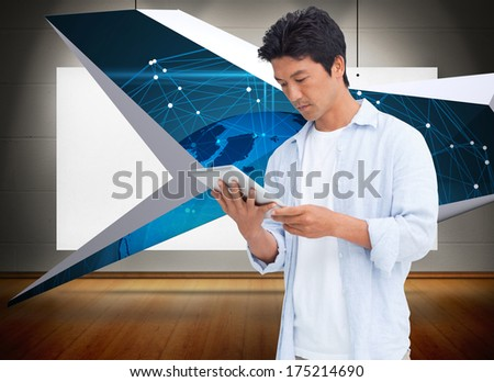 Male looking at his tablet computer against poster hung and exhibited like art - stock photo