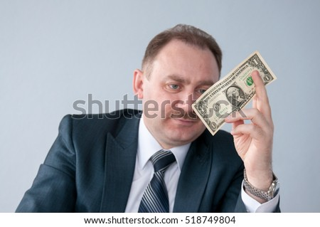Male looks at a dollar in his hand