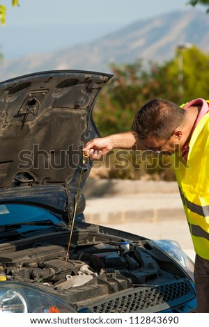 Male making sure his engine is ok for oil - stock photo