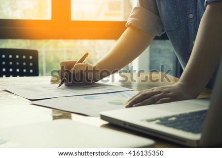 Male manager putting his ideas and writing business plan at workplace,man holding pens and papers, making notes in documents, on the table in office,vintage color,morning light ,selective focus. - stock photo