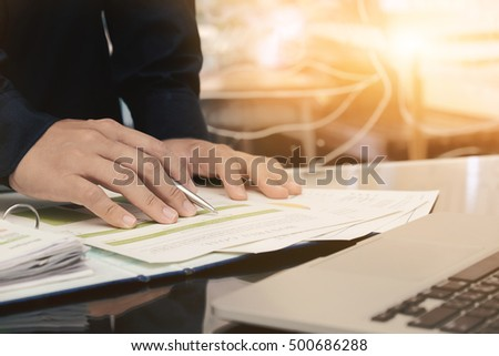 Male manager putting his ideas and writing business plan or analyzing financial documents at workplace,man holding pen making notes in documents, on the table in office,vintage color,morning light.