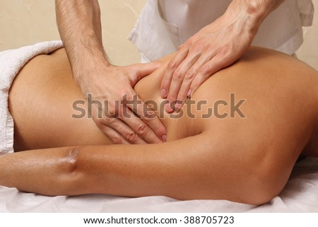 Male masseurs doing back massage, sexy blonde woman. Spa.