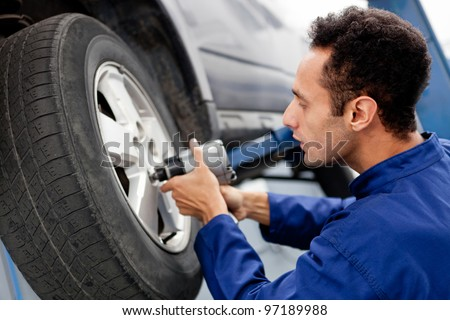 Male mechanic at a car garage fixing a wheel - stock photo