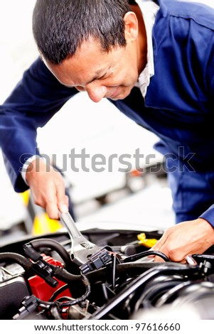 Male mechanic at the garage fixing a car engine - stock photo