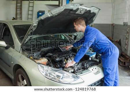 Male mechanic examining car engine with the help of digital tablet - stock photo