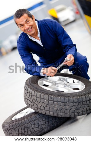 Male mechanic fixing car tire at the garage - stock photo