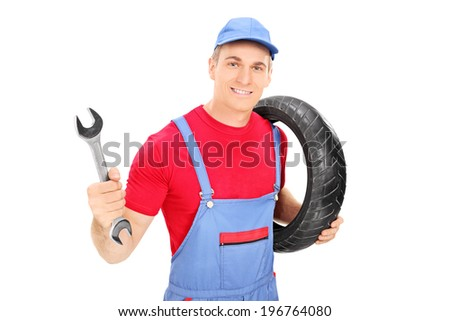 Male mechanic holding a wrench and a tire isolated on white background