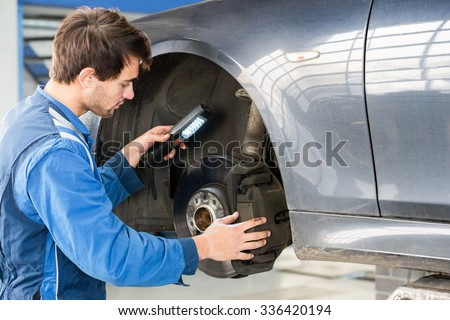 Male mechanic holding flashlight while examining brake disc of car in garage - stock photo