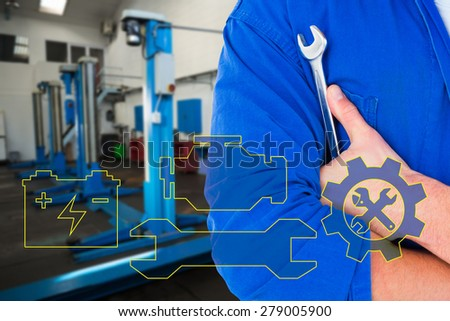 Male mechanic holding spanner on white background against empty work stations - stock photo