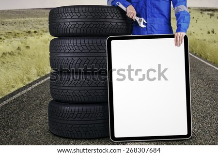 Male mechanic lean on tires while holding an empty board on the road - stock photo