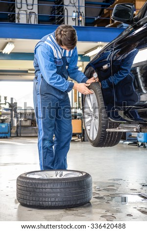 Male mechanic pressing gauge into tire tread to measure its depth at garage at garage - stock photo