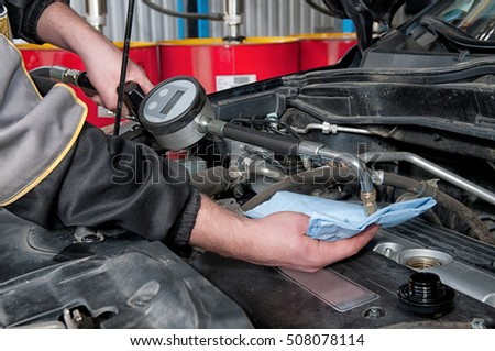 Male mechanic repairing a car engine