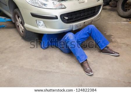 Male mechanic under car - stock photo