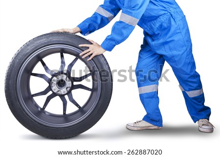 Male mechanic wearing uniform with blue color pushing a tire in the studio, isolated over white - stock photo