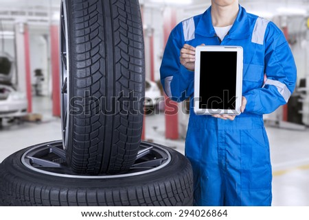 Male mechanic with blue uniform showing empty tablet screen near the tires, shot at workshop - stock photo
