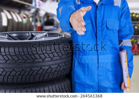 Male mechanic with blue uniform standing in the workshop and offers handshake - stock photo