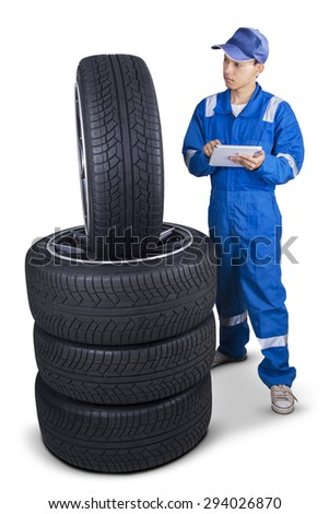 Male mechanic with blue uniform, using a digital tablet to check the tires texture, isolated on white - stock photo