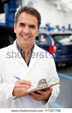 Male mechanic working at a car garage and taking notes - stock photo