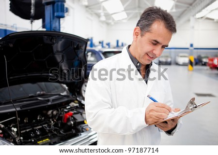 Male mechanic working at a car garage repairing vehicles