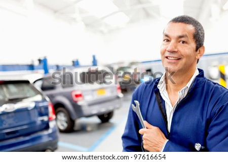 Male mechanic working at a repair shop and holding tools - stock photo