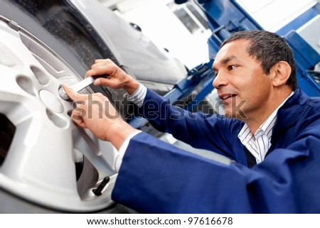 Male mechanic working on car puncture - stock photo