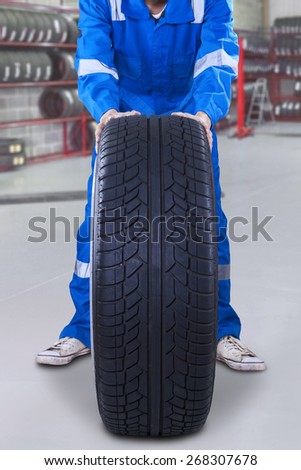 Male mechanic working with a blue uniform and push a tire in the workshop - stock photo