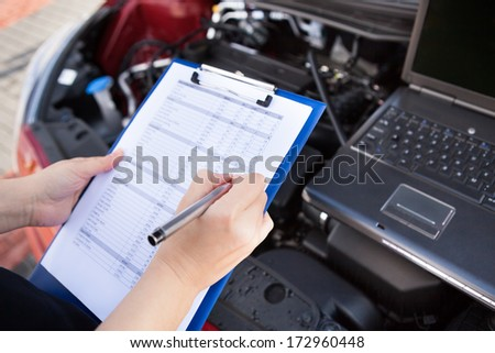 Male Mechanic Writing On Clipboard While Examining Car Engine - stock photo