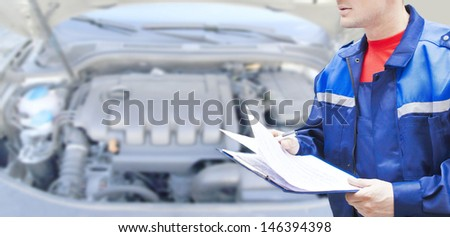 Male mechanic writing on clipboard while examining car engine Copy space for inscription  - stock photo