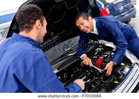 Male mechanics at a car garage fixing an engine - stock photo