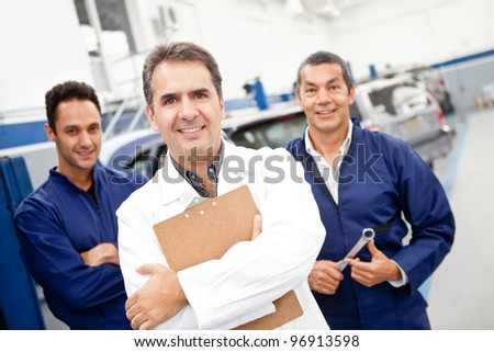 Male mechanics at a care garage smiling - stock photo